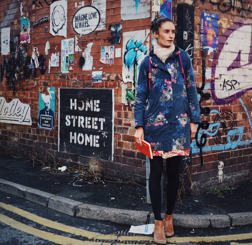 A woman standing in front of street art in Manchester.