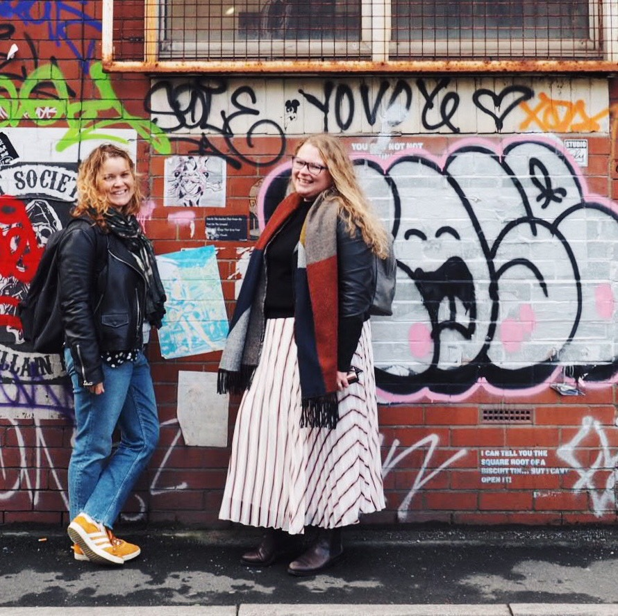 Two women standing in front of street art in Manchester.