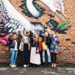 Instacake attendees in front of street art in Manchester.
