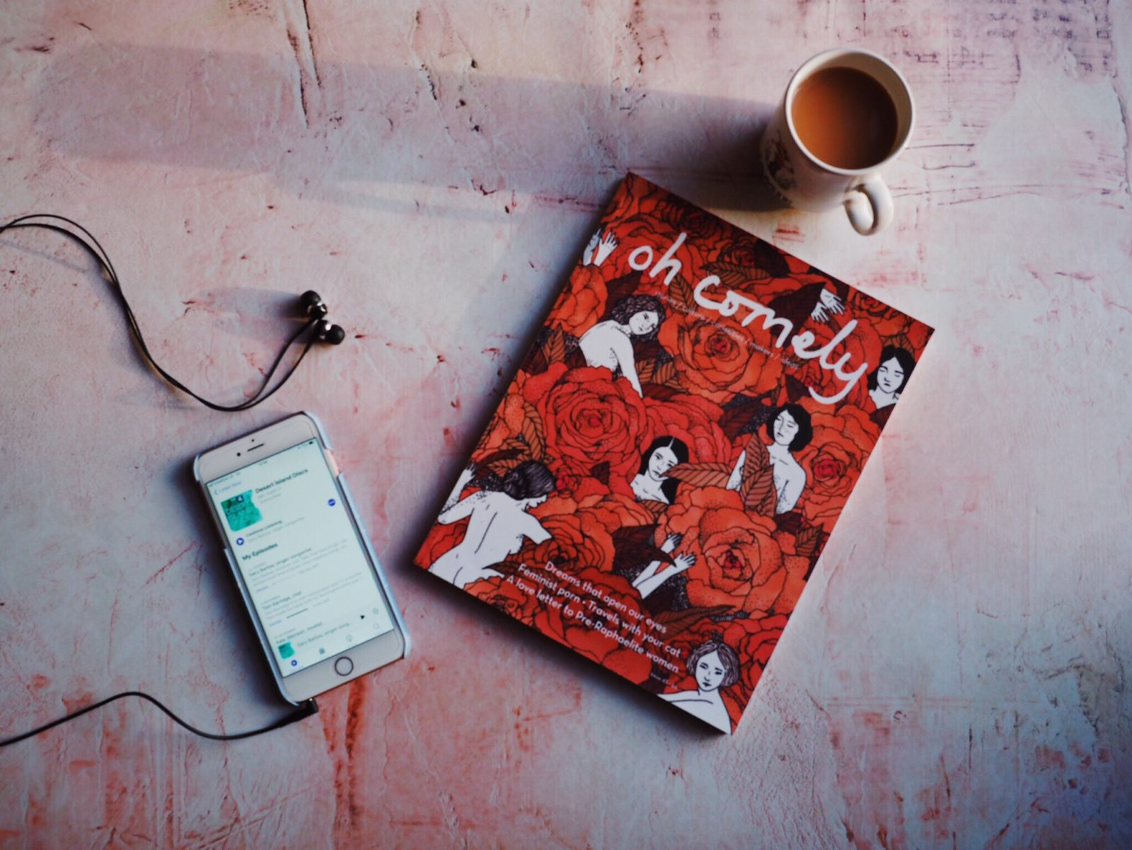Flatlay of cup of tea, magazine and phone.