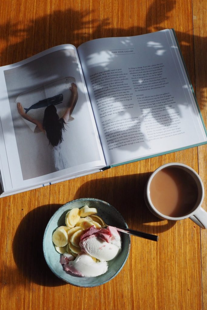 Magazine, bowl and cup of tea.