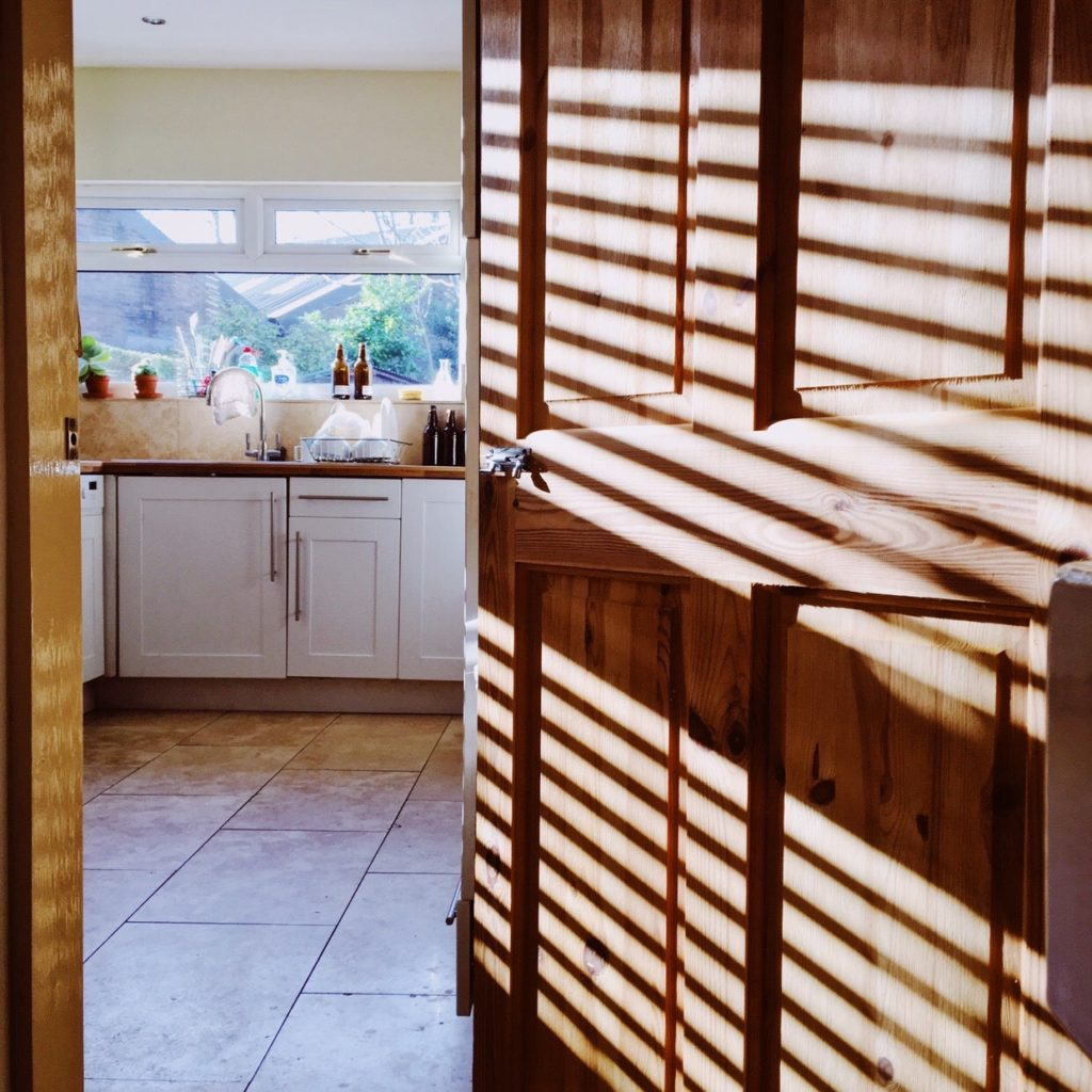 View into a kitchen with light streaming in.