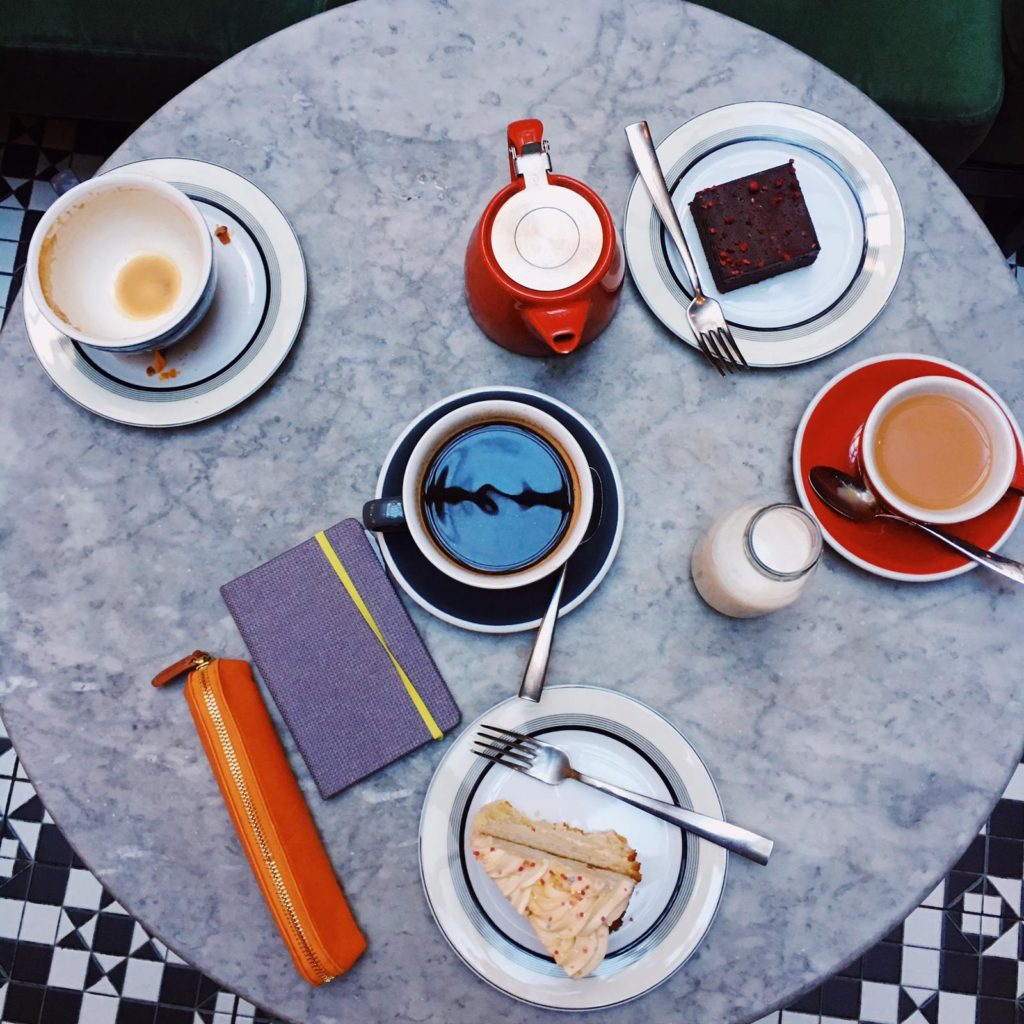 Colourful cakes and coffees on a table.