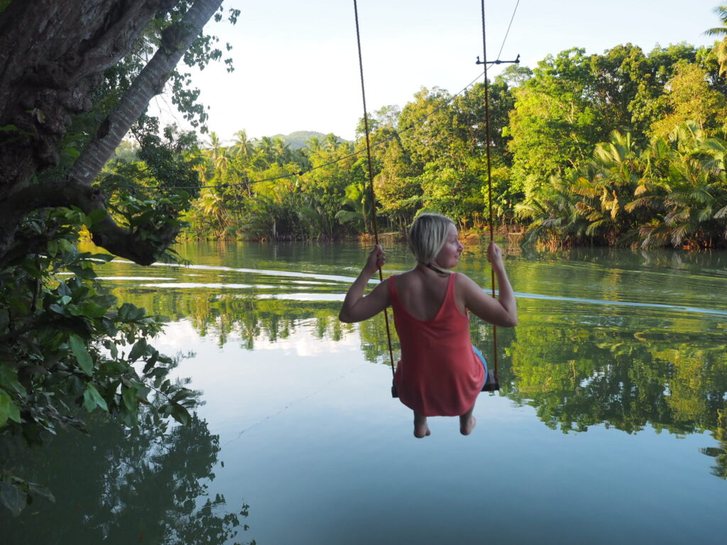 Katya Willems on swing by river in Loboc, Philippines.