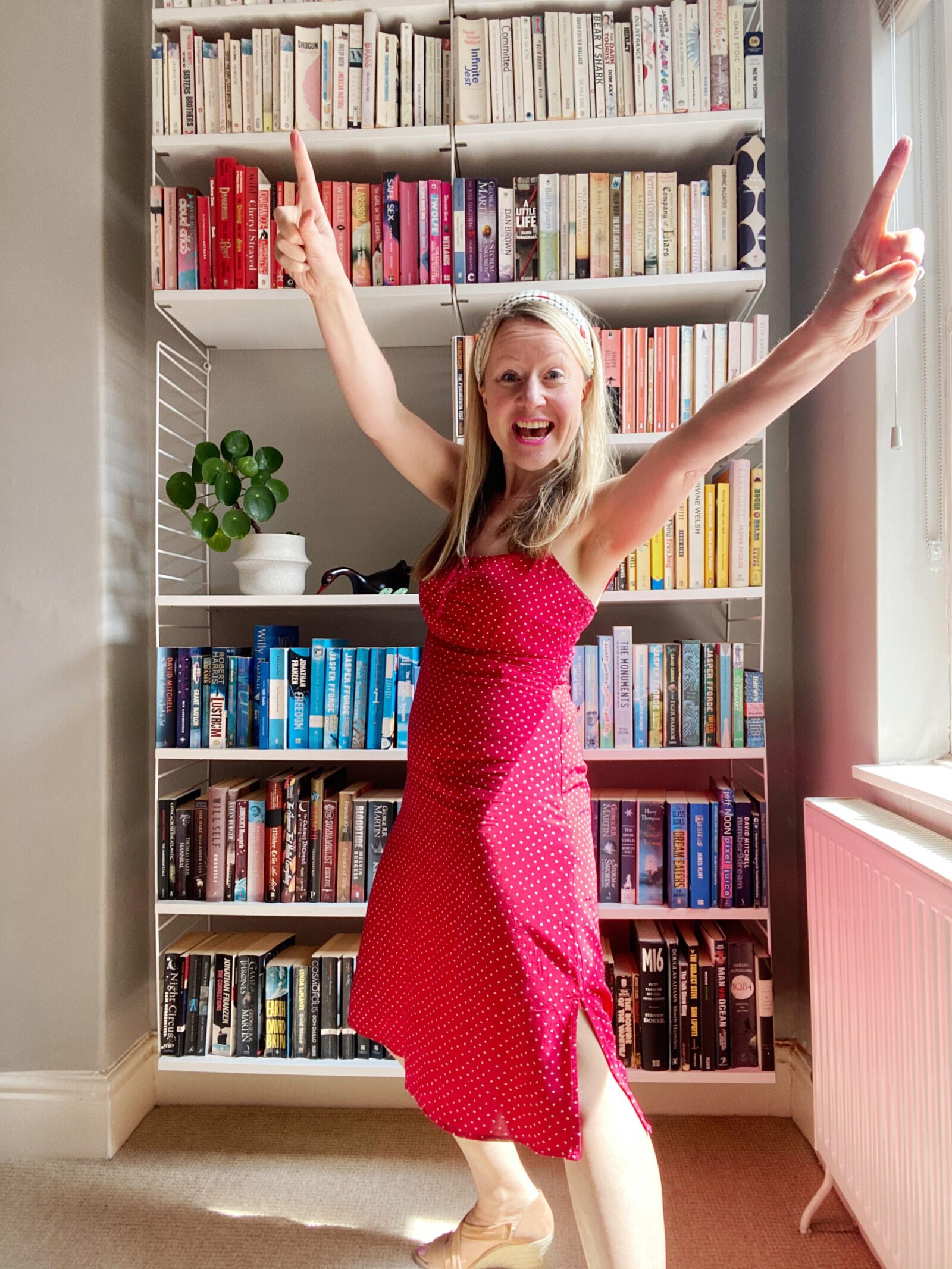 katya willems Instagram trainer in a red dress in front of a colourful bookcase.