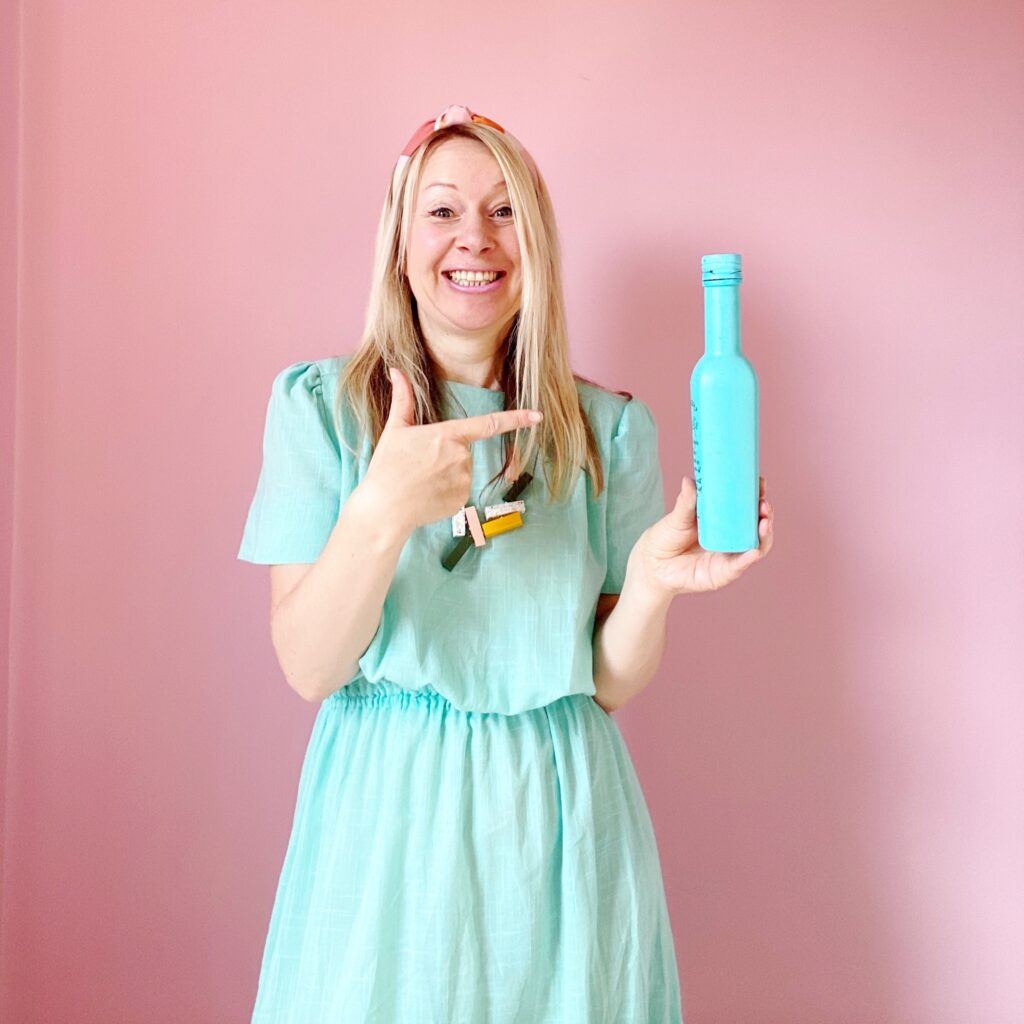 Katya Willems Instgram Trainer in blue dress with a bottle of sauce.