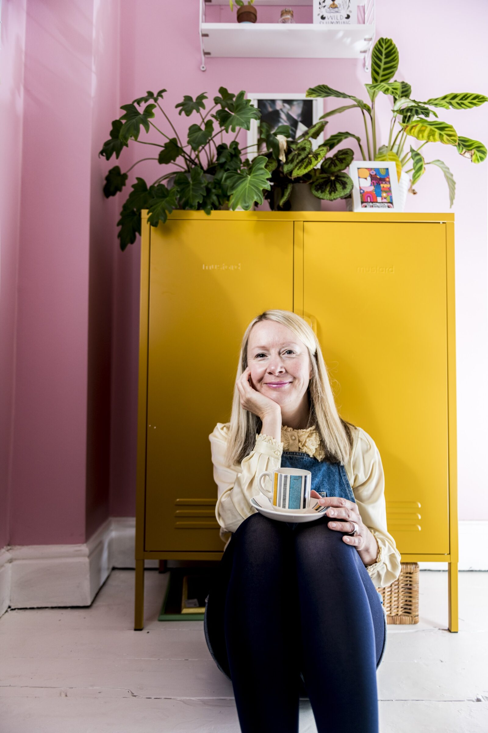 Katya Willems, Instagram expert sitting down in front of a yellow filing cabinet.